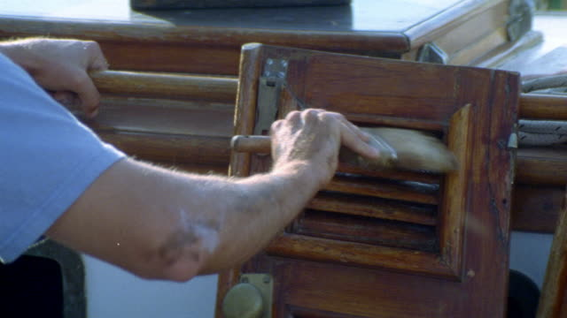 close angle. est. wood shutter. man applying stain or sealant onto shutter. only arm and shoulder of man in shot. appears to be on a boat. - wood stain stock videos & royalty-free footage