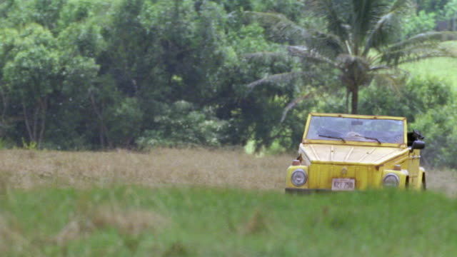 wide angle. old yellow volkswagen driving down dirt road from bg towards camera. camera pans down to right rear wheel as car stops in dirt road. road in grass field. - volkswagen stock-videos und b-roll-filmmaterial