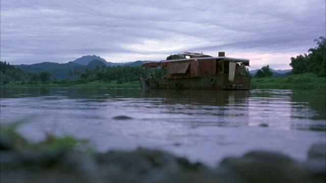 WIDE ANGLE. CAMERA AT GROUND LEVEL ON RIVER BANK. RUNDOWN HOUSEBOAT ANCHORED ACROSS THE WATER IN BG.