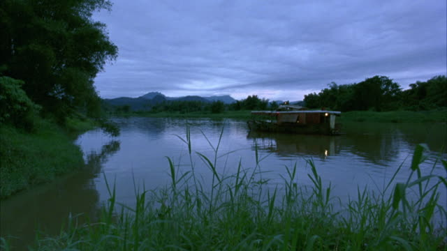 WIDE ANGLE. CAMERA ON RIVER BANK IN RAINFOREST. RUNDOWN HOUSEBOAT ANCHORED IN WATER IN BG. TREES AND GRASS ON SHORE OF RIVER.