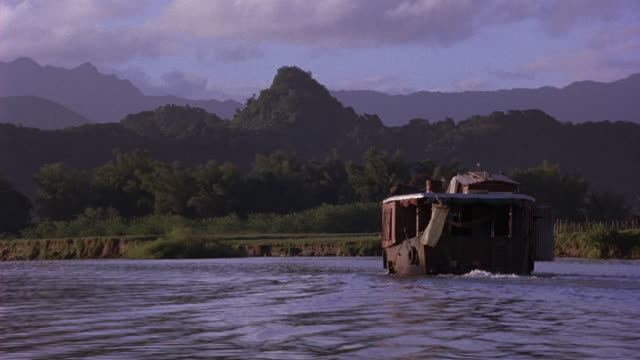 EST WIDE ANGLE. OLD WOODEN HOUSE BOAT SAILS DOWN RIVER. SEE GREEN VEGETATION AND MOUNTAINS IN BG.
