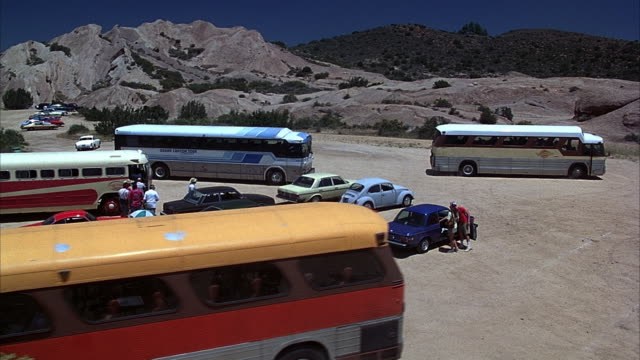 high angle down wide shot - dirt parking lot filled with older cars and buses. all people start to get into vehicles and exit parking lot.  one kid is abandoned in the parking lot. actual location the vasquez rocks in north los angeles county. classic car - vasquez rocks stock videos and b-roll footage