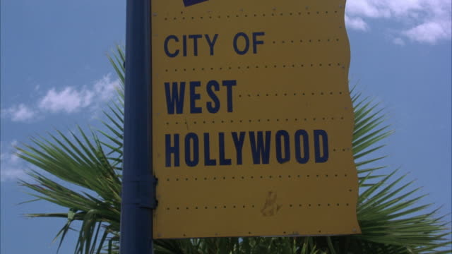 "CLOSE ANGLE OF ""CITY OF WEST HOLLYWOOD"" SIGN. SHOT PANS DOWN TO BEAT-UP DILAPIDATED YELLOW 1969 DODGE CHARGER MUSCLE CAR DRIVING DOWN SUNSET STRIP FROM RIGHT TO LEFT."