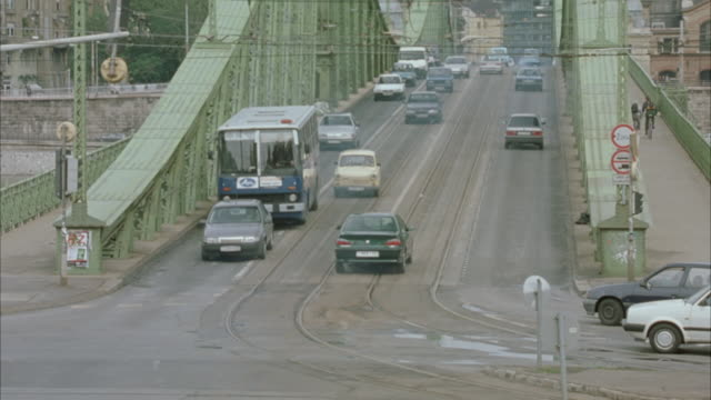 WIDE ANGLE OF LIBERTY BRIDGE AS CARS DRIVE DOWN.  TWO TAKES.  IN SECOND TAKE,  GREEN PEUGEOT BEGINS TO DRIVE UP THE ROAD THEN EXPLODES. EXPLOSIONS.