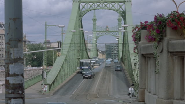 WIDE ANGLE OF LIBERTY BRIDGE AS CARS DRIVE DOWN.  GREEN PEUGEOT DRIVES UP THE CENTER ALONG THE TRAM TRACK AND EXPLODES. EXPLOSIONS.
