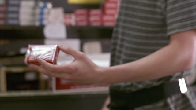 close angle. insert of store clerk holding up pack of 'pall mall' cigarettes. only waist of clerk in shot. clerk holds out pack of cigarettes multiple times. - assistant stock videos & royalty-free footage