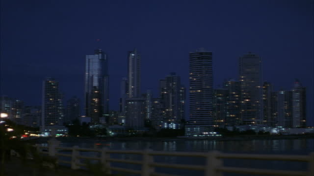 medium angle. front plate. camera driving down highway in panama. highway runs along coastline. camera pans right to panama city skyline in bg. pans back and forth between highway and skyline. driving into downtown area. neg cut. - パナマ点の映像素材/bロール