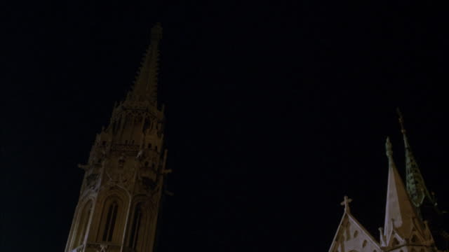 matthias church in budapest at night. pan up to steeple. pan down to street in front of church. - steeple stock videos & royalty-free footage