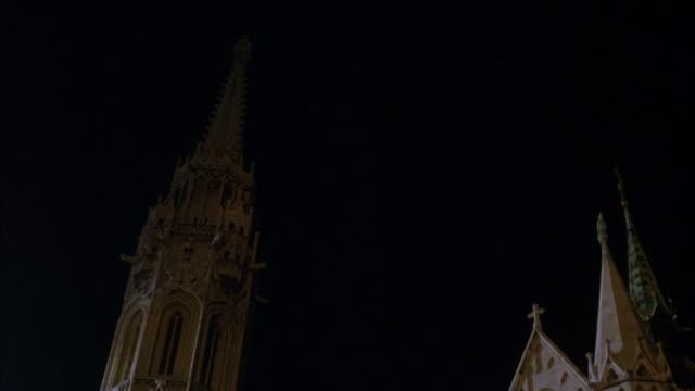 stockvideo's en b-roll-footage met matthias church in budapest at night. pan up to steeple. pan down to street in front of church. - kerktoren