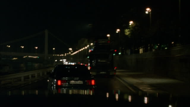 vidéos et rushes de driving pov following car transport truck.  car weaves in and out of oncoming traffic.  stunt actors shoot guns from the transport truck at car.  stunt actors in second car shoot at transport truck. - budapest