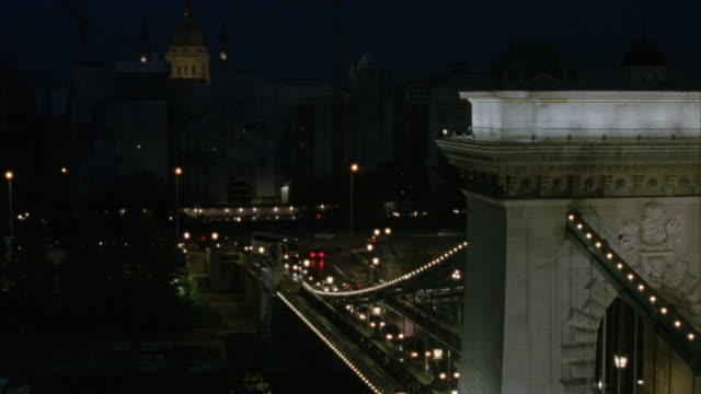 wide angle. chain bridge at night as cars drive on it. buda castle or royal palace  in front of bridge in background - royal palace of buda stock videos & royalty-free footage
