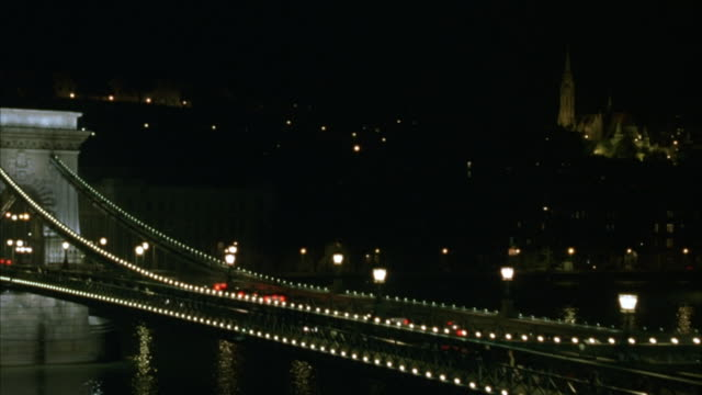 aerial. wide angle of chain bridge over the danube river. pans right to left across the bridge. shot moves over bridge toward matthias church. zoom in on matthias church. light reflects in water. - river danube stock videos & royalty-free footage