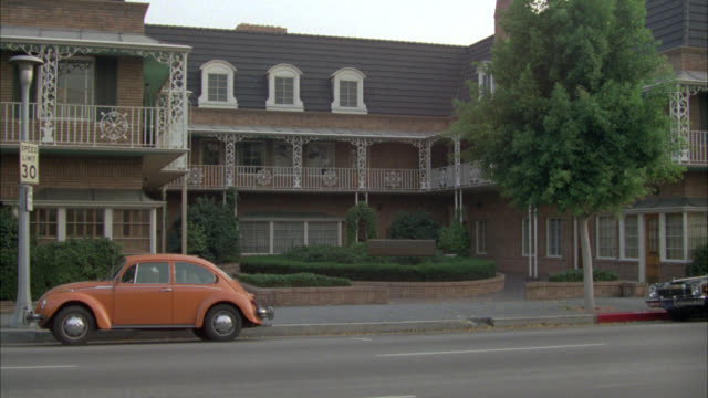"""zoom in on law office building, new orleans-style with mansard roof with sign that reads """"law offices"""". cars driving by on street in fg. building is located on green street in pasadena. attorney offices. brick buildings. volkswagen beetle car parked in fr - volkswagen stock-videos und b-roll-filmmaterial"""