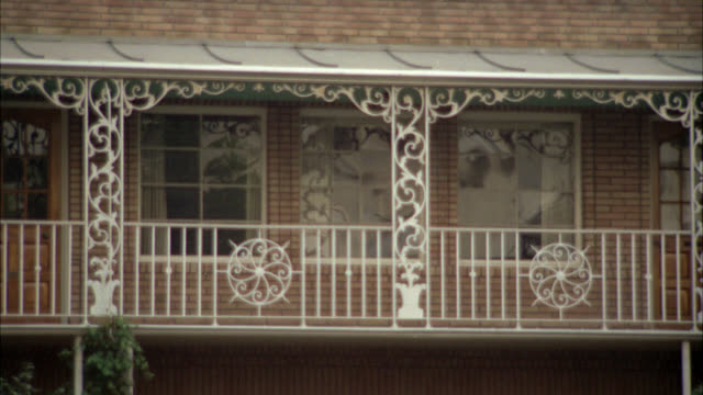 medium angle of second story window in new orleans style, brick office building with ornate wrought iron railings. could be used for law offices. building is located on green street in pasadena. - fensterfront stock-videos und b-roll-filmmaterial