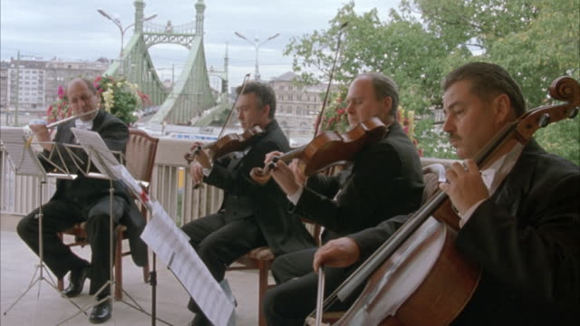 est medium angle on four male musicians in tuxedos, a classical quartet or chamber ensemble similar to a string quartet.   one musician is playing the flute, one the violin,  one the viola, and one the cello. they stop, turn the page, and continue to play - liberty bridge budapest stock videos & royalty-free footage