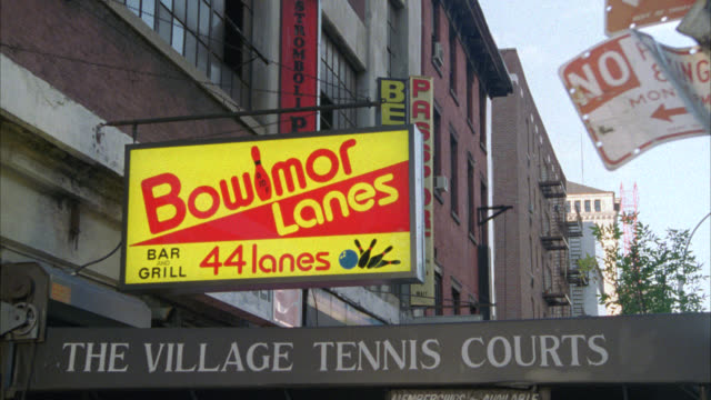 vídeos de stock, filmes e b-roll de pan down from sign for bowlmor bowling alley to sign on awning for village tennis courts. sports. matching nx is 1235-e. greenwich village. people or pedestrian on sidewalk. - cancha de jogo de boliche