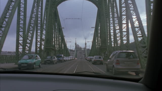 vidéos et rushes de wide angle driving pov on liberty bridge in budapest. drives over bridge and stops at intersection at the other end of the bridge. - budapest