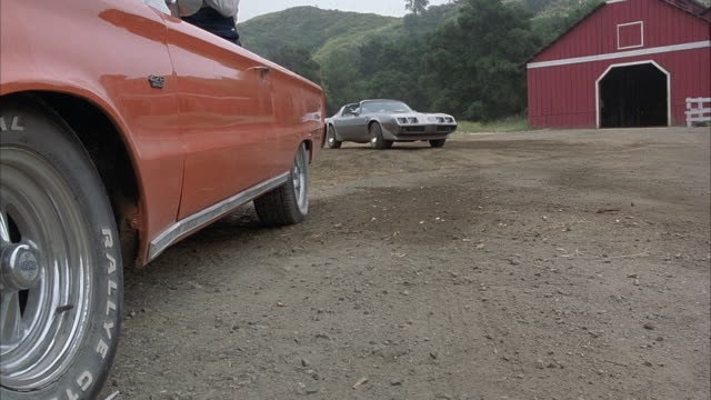 medium angle of 1979 pontiac firebird trans am car pulling up alongside a red 1967 plymouth belvedere gtx convertible in front of red barn. - land vehicle stock videos & royalty-free footage