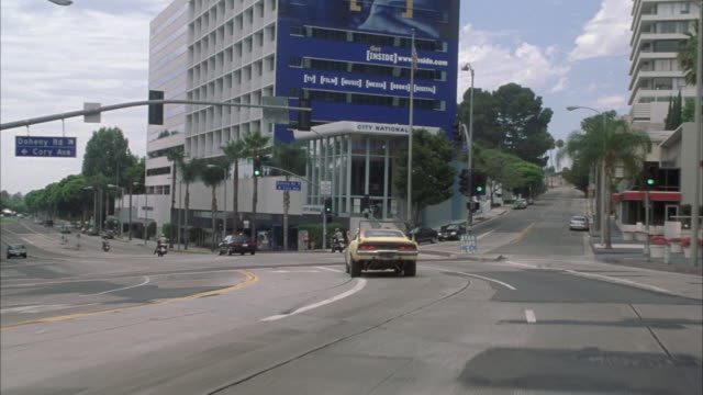 vídeos de stock e filmes b-roll de process plate straight forward of yellow 1969 dodge charger driving west on sunset strip, through west hollywood towards beverly hills. car gets into left turning lane. muscle cars. - west hollywood