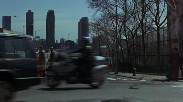 MEDIUM ANGLE DRIVING POV STRAIGHT FORWARD OF NEW YORK CITY STREET. SKYSCRAPER BUILDINGS IN BG. TREES WITH BARE BRANCHES ON RIGHT SIDE OF STREET. POV STOPS AS POLICE MOTORCYCLES, COULD BE POLICE ESCORT OR MOTORCADE, DRIVE FROM RIGHT TO LEFT ACROSS SCREEN T