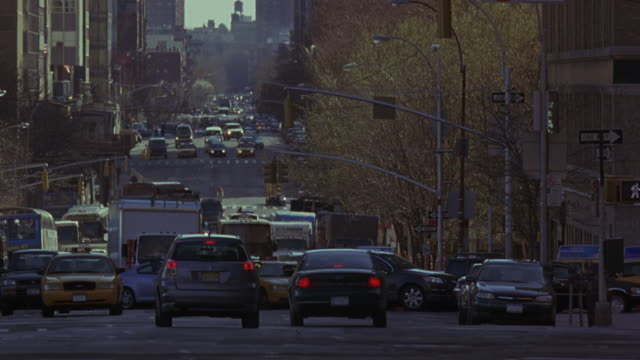 WIDE ANGLE OF CARS, TAXIS, CITY BUSES DRIVING THROUGH INTERSECTION OF 6 LANE CITY STREET IN NEW YORK CITY. HIGH RISE OFFICE OR APARTMENT BUILDINGS AND TREES WITH BARE BRANCHES OR AUTUMN LEAVES ON BOTH SIDES OF STREET. POLICE MOTORCYCLES, COULD BE POLICE E