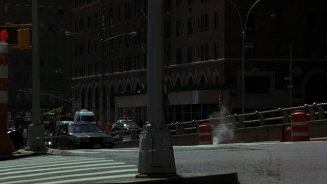 MEDIUM ANGLE OF CARS DRIVING UP RAMP OF NEW YORK CITY STREET. MULTI-STORY BRICK OFFICE OR APARTMENT BUILDING IN BG. NYPD POLICE MOTORCYCLES AND FORD MUSTANG POLICE CAR WITH BIZBAR, FLASHING LIGHTS, COULD BE POLICE ESCORT OR POLICE MOTORCADE,  SPEED UP RAM
