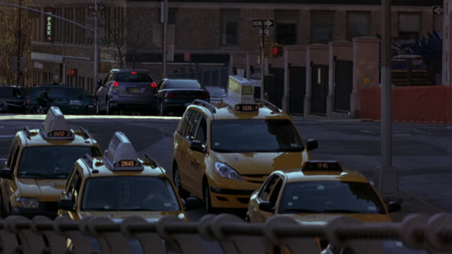 WIDE ANGLE OF CARS, TAXIS DRIVING ON NEW YORK CITY STREET. NYPD POLICE MOTORCYCLES AND FORD MUSTANG POLICE CAR WITH BIZBAR, FLASHING LIGHTS, PULL OUT FROM RIGHT SIDE OF SCREEN, SPEED ACROSS STREET AND UP RAMP TOWARDS CAMERA. COULD BE POLICE ESCORT OR MOTO