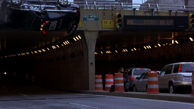 wide angle of nypd ford mustang police car with bizbar, flashing lights hanging over edge of overpass of first avenue tunnel in new york city. cars, taxis drive through tunnel entrance. police drops from overpass and crashes onto street below. a black lin - lincoln town car stock videos and b-roll footage