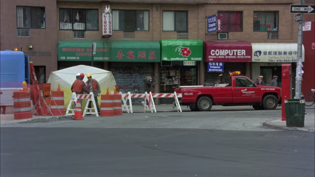 WIDE ANGLE OF NYC STREET UNDER CONSTRUCTION. WORKERS WITH HARDHATS STAND AROUND. STOREFRONTS OR BUILDINGS WITH AWNINGS IN BG. NYPD OFFICERS ON MOTORCYCLES WITH FLASHING LIGHTS SPEED ONTO CURVED STREET. OFFICERS PAUSE AROUND CARS. TRASH BAGS ON SIDEWALK.