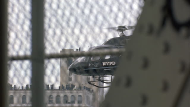 vídeos de stock, filmes e b-roll de close angle of nypd police helicopter through chain link fence on manhattan bridge. iron girder out of focus in fg. building out of focus in bg. could be church or warehouse. - chain bridge suspension bridge