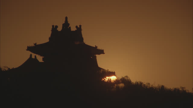 wide angle of sun rising over pagoda. chinese architecture. asia. willow trees visible. - pagoda stock videos & royalty-free footage