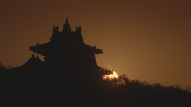 vídeos de stock e filmes b-roll de wide angle of sun rising over pagoda. chinese architecture. asia. willow trees visible. - árvore de folha caduca