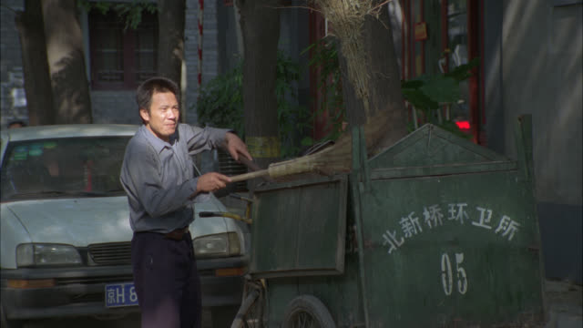MEDIUM ANGLE OF MAN WITH BROOM SWEEPING STREETS. DUMPSTER WITH CHINESE CHARACTERS. ASIA. COULD BE URBAN AREA. PEOPLE SIT ON STEPS.