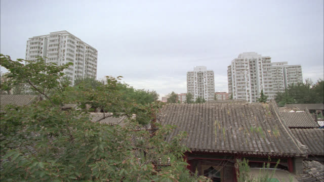 pull back from wide angle of multi-story apartment buildings in urban area to lower class pagoda style house. asia. courtyard or backyard of house visible. telephone pole abd trees in fg. - courtyard stock videos & royalty-free footage