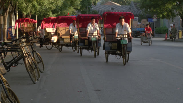 zoom in on men pedaling empty pedicabs or cycle rickshaws in city street. - risciò video stock e b–roll