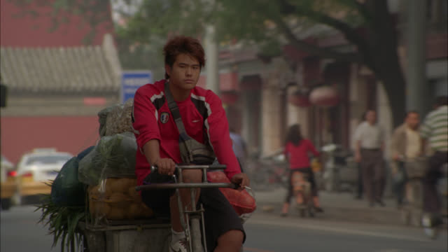 MEDIUM ANGLE OF MAN RIDING BICYCLE IN CITY STREET, TOWING ATTACHED CART WITH GROCERIES OR FOOD.