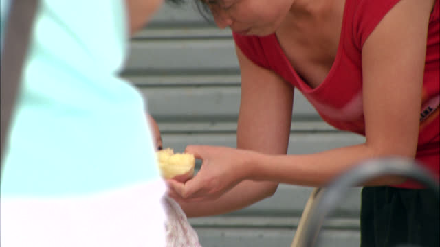CLOSE ANGLE OF WOMAN OR MOTHER FEEDING BABY A PIECE OF FRUIT.