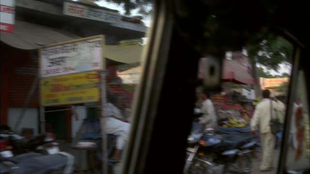 WIDE ANGLE MOVING POV OF LOWER CLASS RURAL AREA. BUSINESSES LINE STREET. FRUIT STANDS. COULD BE MARKETPLACE PEOPLE SIT IN DOORWAYS AND STAND AT EDGE OF STREET. CARS AND TRUCKS PARKED. POOR. COULD BE SLUM. COULD BE VILLAGE.