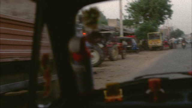 WIDE ANGLE MOVING POV OF LOWER CLASS RURAL AREA. BUSINESSES LINE STREET. PEOPLE SIT IN DOORWAYS AND STAND AT EDGE OF STREET. CARS AND TRUCKS PARKED. CATTLE OR COWS VISIBLE. POOR. COULD BE SLUM. COULD BE VILLAGE.