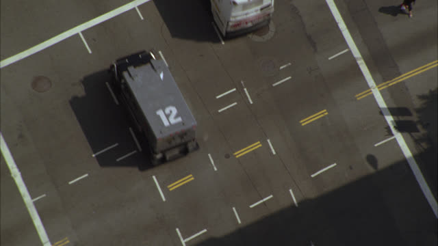 aerial of armored truck driving on city streets through downtown. cars driving through intersection. - armored truck stock videos and b-roll footage