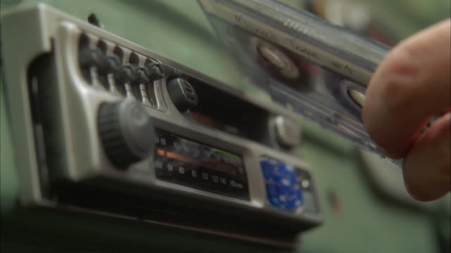 vídeos de stock, filmes e b-roll de close angle of hand putting tape in cassette player. car radio. - rádio eletrônico de áudio