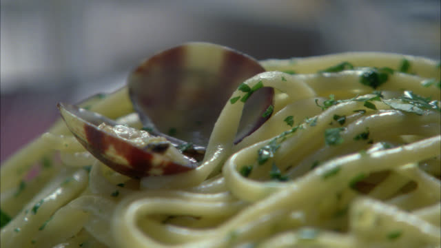 CLOSE ANGLE OF PERSON SPEARING MEAT OF CLAM FROM ITS SHELL WITH A FORK. LINGUINI OR PASTA. ITALIAN FOOD. SEAFOOD.