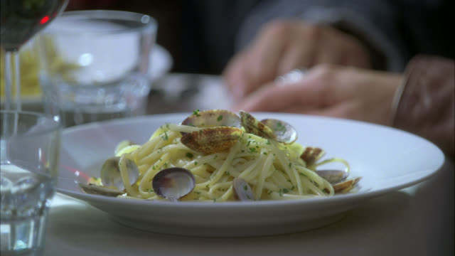 CLOSE ANGLE OF WAITER PLACING PLATE OF LINGUINI WITH CLAMS OR PASTA ON TABLE IN UPPER CLASS RESTAURANT. FOOD. SERIES.