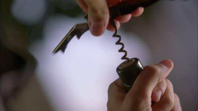 close angle of woman's hands turning corkscrew to open wine bottle. - wine bottle stock videos & royalty-free footage