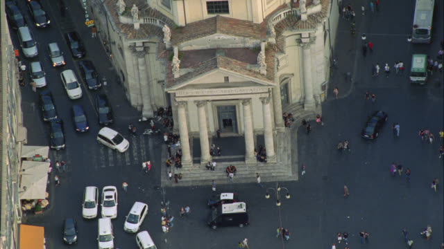AERIAL OF CATHOLIC CHURCH OF SANTA MARIA DI MONTESANTO IN PIAZZA DEL POPOLO WITH OBELISK IN CENTER. TOWN SQUARE OR PLAZA. MULTI-STORY OFFICE OR APARTMENT BUILDINGS. RED TILE ROOFS. LANDMARKS.