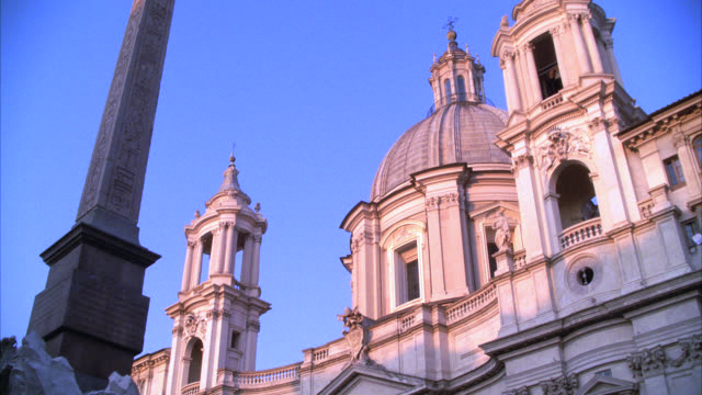 UP ANGLE OF DOMED BUILDING, CATHOLIC BASILICA CHURCH OF SANT'AGNESE OF AGONE, AND OBELISK ON FOUNTAIN OF THE FOUR RIVERS. PIAZZA NAVONA.