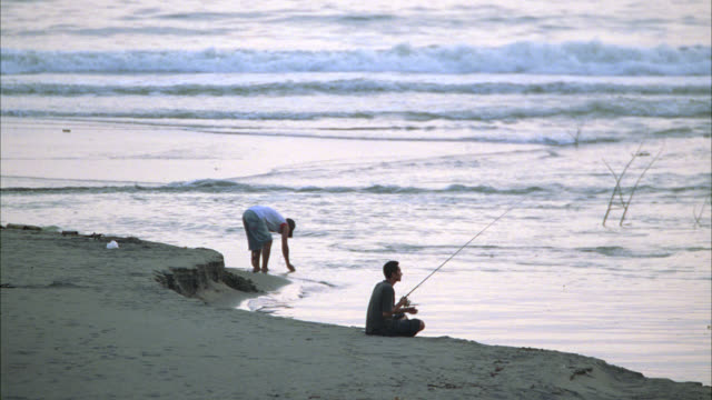 wide angle of men fishing on beach or shore. ocean in bg. fishing poles. - fishing rod stock videos & royalty-free footage