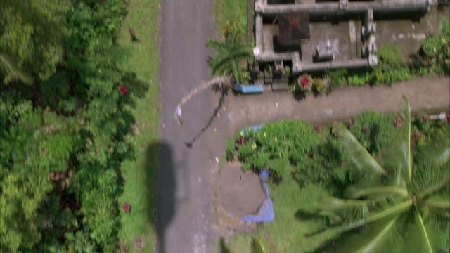 AERIAL OVER SMALL COUNTRY ROAD IN RURAL AREA. PALM TREES AND TROPICAL PLANTS. HOUSE AND JEEP OR SUV.