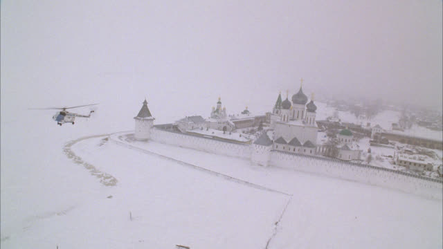 AERIAL OF MAKARIEV MONASTERY NEAR NIZHNY NOVGOROD ON THE FROZEN VOLGA RIVER. COULD BE FORTRESS, CASTLE, CONVENT, RUSSIAN ORTHODOX CHURCH OR CATHEDRAL. HELICOPTER. SNOW. WALLS WITH GUARD TOWERS, TURRETS. ONION DOMES. RUSSIAN COUNTRYSIDE OR RURAL AREA.