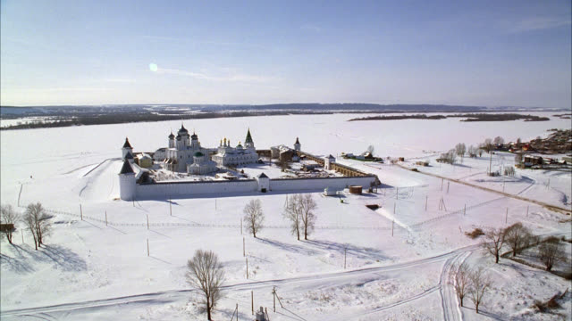 AERIAL OF MAKARIEV MONASTERY NEAR NIZHNY NOVGOROD ON THE VOLGA RIVER. COULD BE FORTRESS, CASTLE, CONVENT, RUSSIAN ORTHODOX CHURCH OR CATHEDRAL. SNOW. WALLS WITH GUARD TOWERS, TURRETS. ONION DOMES. HELICOPTER FLIES OVER RUSSIAN COUNTRYSIDE OR RURAL AREA. M